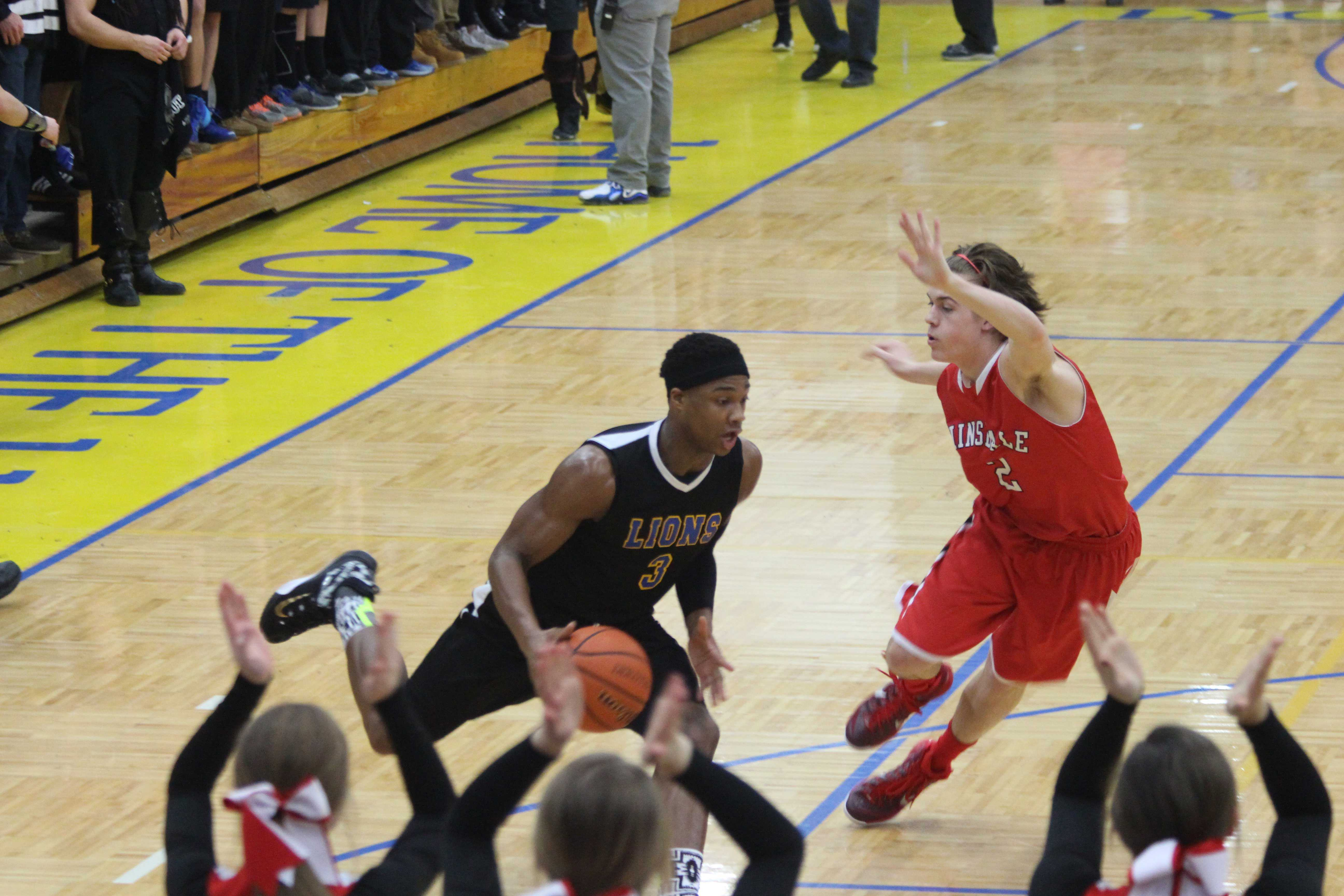 Jaquan Phipps '15 drives on a Hinsdale Central defender.