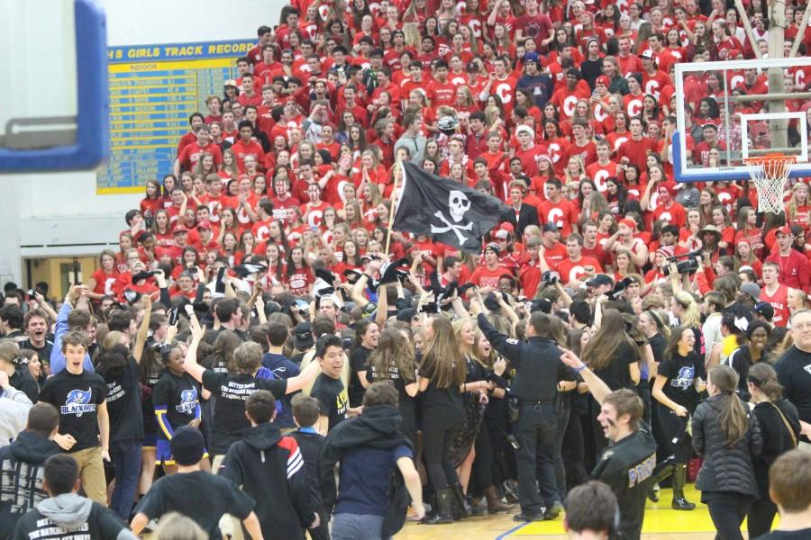 Students+storm+the+court+after+Swinehart+hit+his+half-court+shot.+He+is+visible+in+the+bottom+right+with+eye-black+on+his+face.+