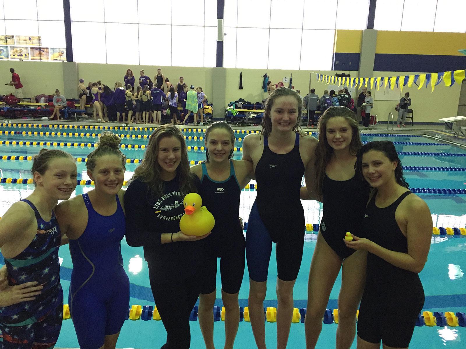 Wimmer stands center holding a rubber duck amongst fellow varsity teammates