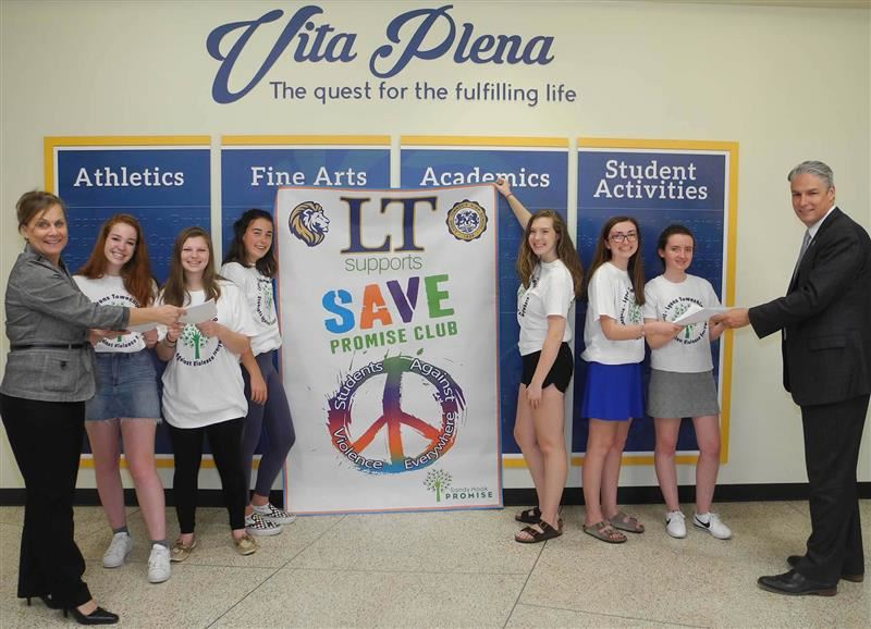 Members of the LT Save club pose with administrators Dr. Waterman and Therese Nelson in front of a sign for their club