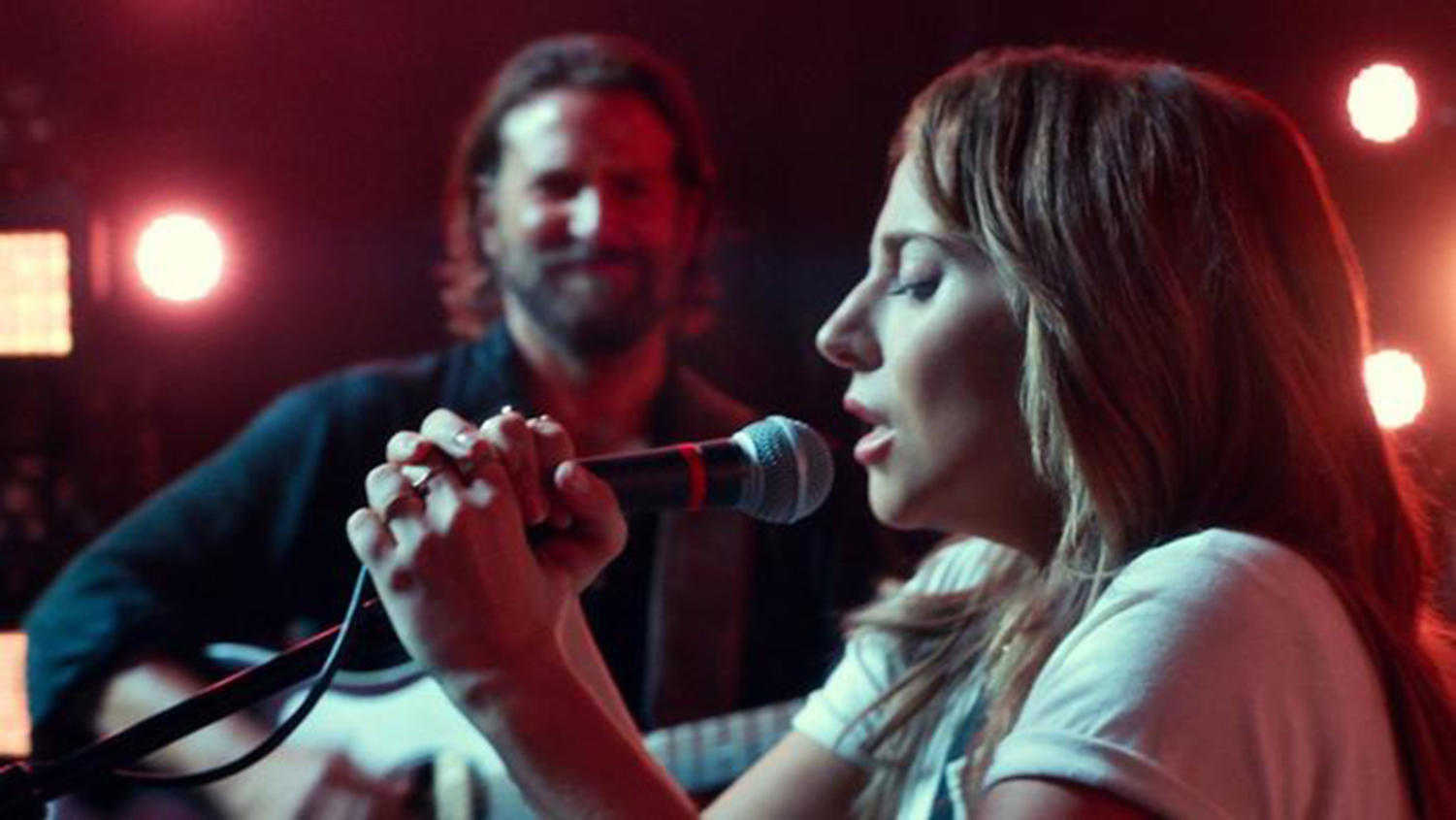 Lady Gaga's character, Ally, takes the mike onstage as Bradley Cooper looks on (Warner Bros. Pictures).