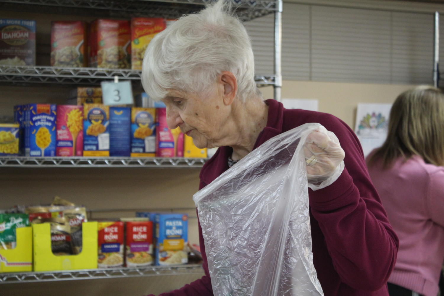 Marylin Chopp hands out bagels at the St. Cletus food pantry (Lonnroth/LION).