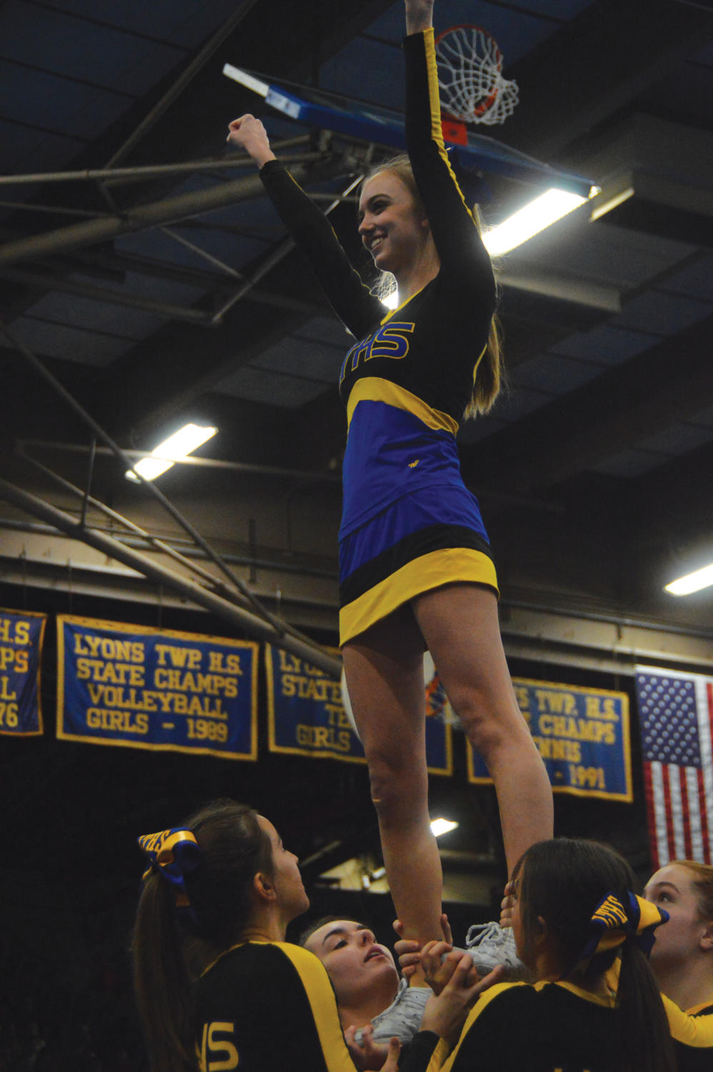 Cheerleader+stands+triumphantly+on+top+of+the+human+pyramid.