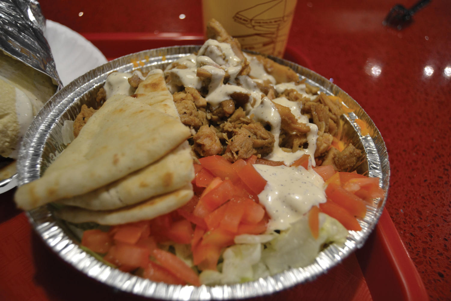 "The chicken platter from ""The Halal Guys'"" that includes basmati rice, lettuce, tomato, hummus, and white sauce. (Bonfiglio/LION)"