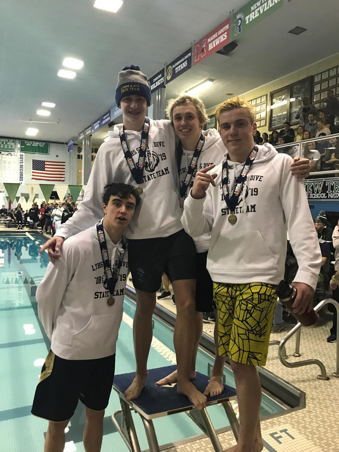 Medley relay team posing with their medals after winning the state title at New Trier on Feb. 23 (Donatelli).