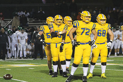 Offensive line watches coaches play run down during Glenbard West game on Bennett field on Oct. 4 (Sorice/LION).