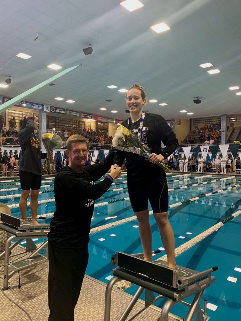 Cal Dunn '20 shakes coach Scott Walker's hand after her first place win on Nov. 23 (photo courtesy of Erin Rodriguez).