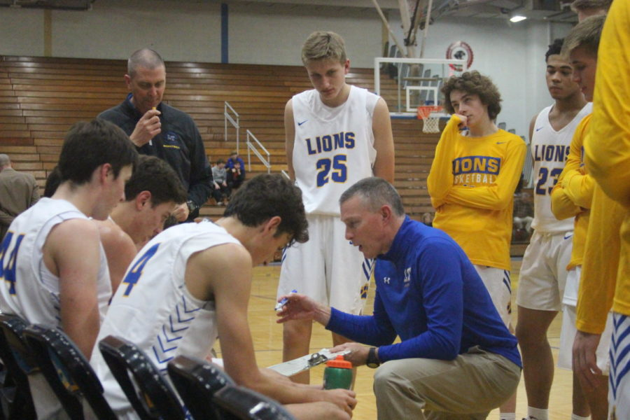 Coach Tom Sloan draws up plays in timeout during a game against Maine South on Nov. 27 in the NC field house (Layden/LION).