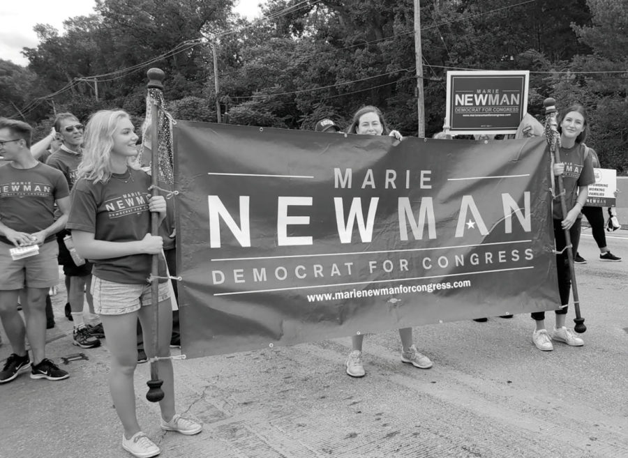 Students Sophia Tarasuk (pictured to the left of the banner) and Jaden Ownby (pictured to the right of the banner) walk for Marie Newman's campaign (courtesy of Ownby).