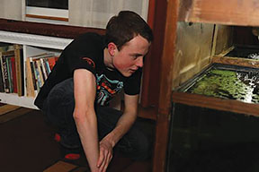 August Duwell '20 observes species of fish in his fish farm (photo courtesy of Ellie Pendleton).