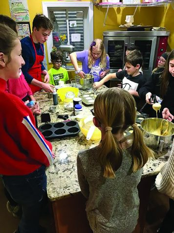 Genaro Giovingo-Mino patiently  teaches his  young students to bake cupcakes over the  summer of 2019 in his home kitchen (photo courtesy of Giovingo-Mino).