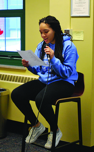 Student reads her work during Open Mic Cafe