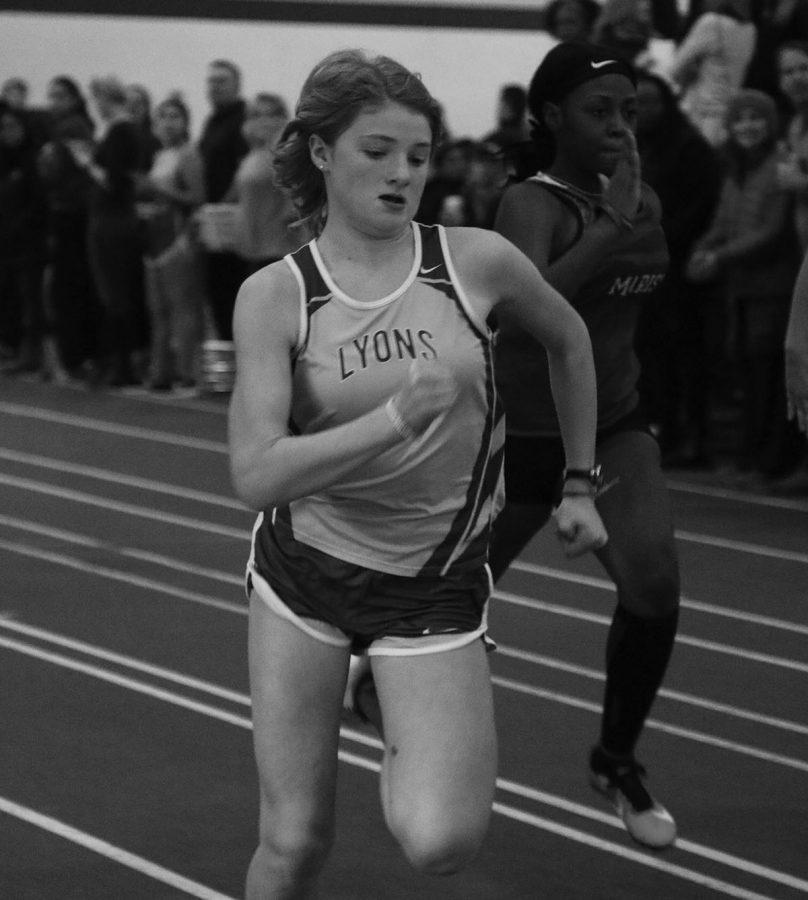 Caroline Vear '22 sprints during a race in the SC fieldhouse (Buckendahl/TAB).