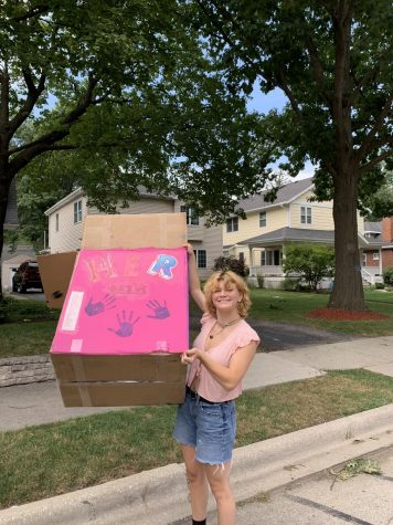 Adeline Volz poses with the HER Drive donation bin (photo courtesy of Volz).