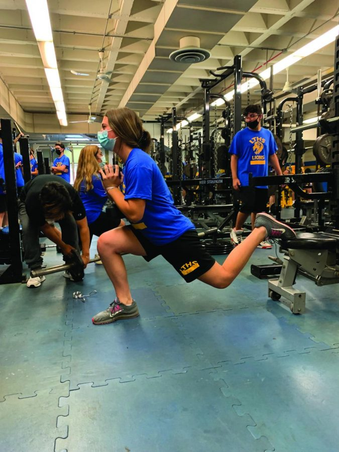 Kaitlyn Filkins 24 uses weights during sixth period Strength Training class (photo courtesy of Bryan Bergman).